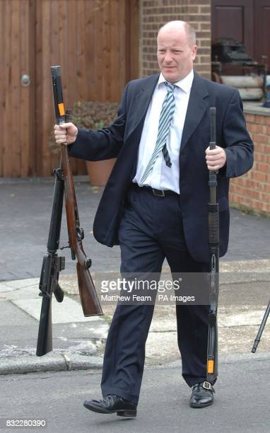 A Metropolitan Police officer removes firearms from the home of a 55 year old man in Dartford Kent PRESS ASSOCIATION Photo Picture issue date...