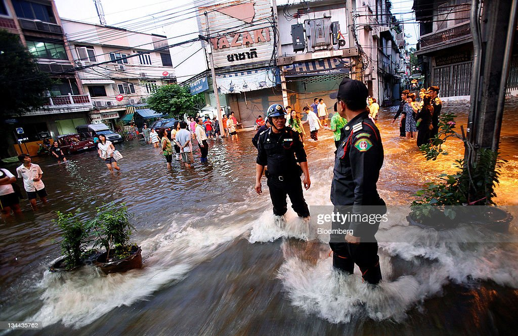 Metropolitan Police officers stand on a flooded road in Bangkok, Thailand, on Wednesday, Oct. 26, 2011. Thai Prime Minister Yingluck Shinawatra said a '50-50' chance remained that inner Bangkok would avoid flooding as a deluge approaches the city and a coming high tide pushes up water levels. Photographer: Dario Pignatelli/Bloomberg via Getty Images