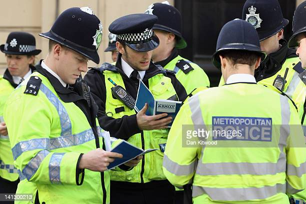 Metropolitan Police read leaflets detailing their new Liason officer strategy ahead of a march on March 14 2012 in London England Students have been...