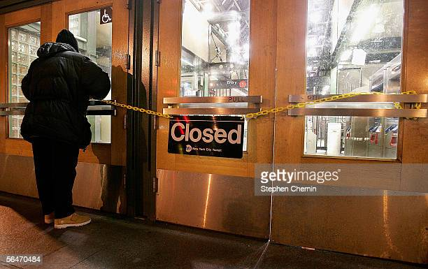Metropolitan Transit Authority worker strings a yellow chain with a closed sign across the doors of the 72nd street subway station on December 20...