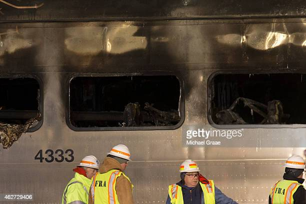 Metropolitan Transportation Authority workers stand beside a burned out train car following a crash on February 3 2015 in Valhalla New York A...
