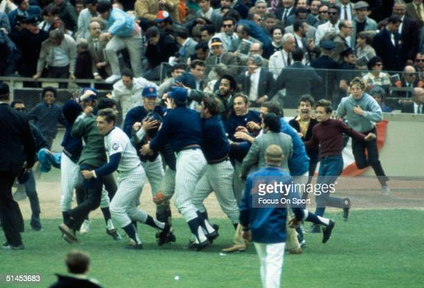 Mets players celebrate as jubilant fans rush the Stadium after the Mets won the 1969 World Series against the Baltimore Orioles at Shea Stadium in...