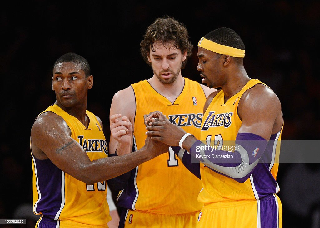 Metta World Peace #15 and Pau Gasol #16 of the Los Angeles Lakers help Dwight Howard #12 with his contact lens during the basketball game against Phoenix Suns at Staples Center on November 16, 2012 in Los Angeles, California.