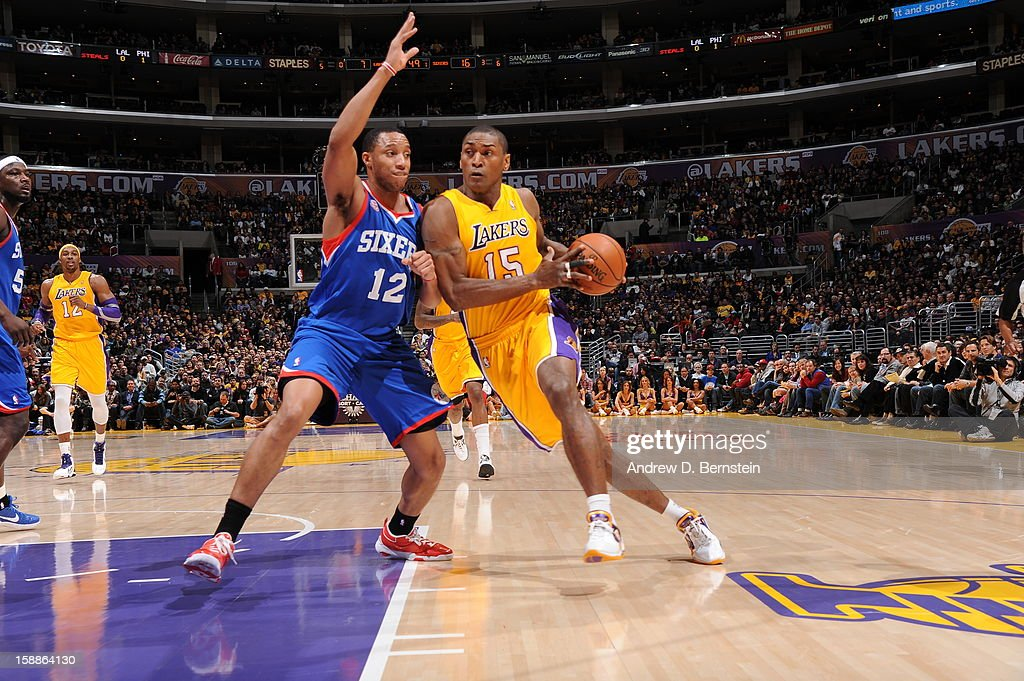 Metta World Peace #15 of the Los Angeles Lakers drives to the hoop against Evan Turner #12 of the Philadelphia 76ers at Staples Center on January 1, 2013 in Los Angeles, California.