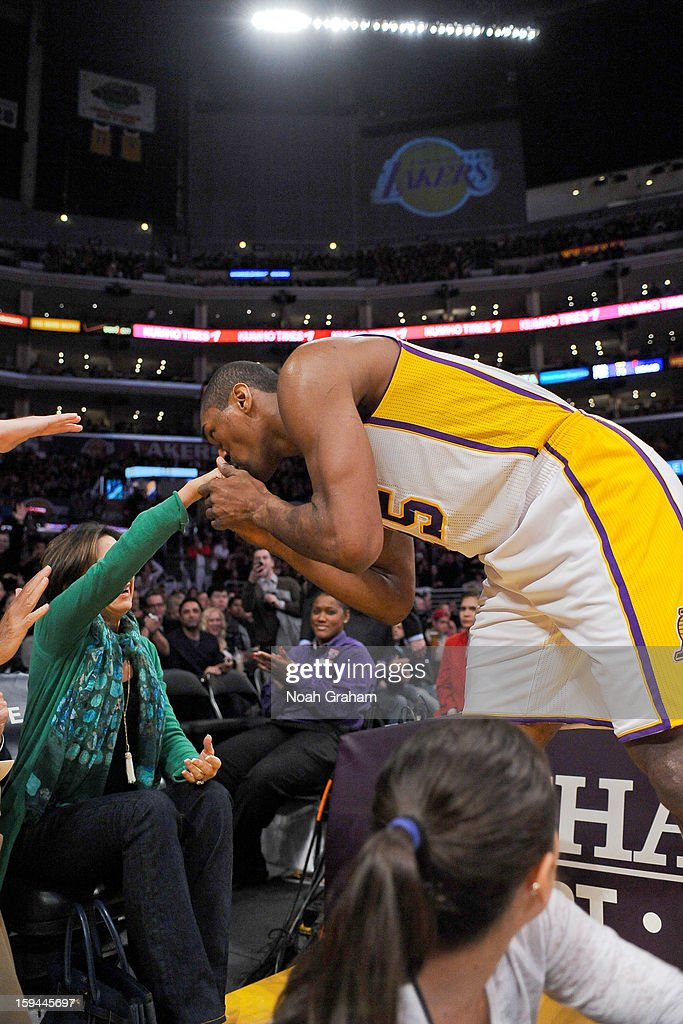 Metta World Peace #15 of the Los Angeles Lakers kisses the hand of a fan after dunking against the Cleveland Cavaliers at Staples Center on January 13, 2013 in Los Angeles, California.