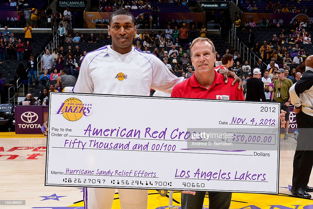 Metta World Peace #15 of the Los Angeles Lakers presents a check on behalf of his team to the American Red Cross for Hurricane Sandy Relief Efforts before playing the Detroit Pistons at Staples Center on November 4, 2012 in Los Angeles, California.