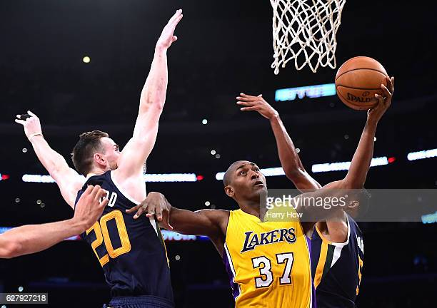 Metta World Peace of the Los Angeles Lakers scores between Gordon Hayward and Rodney Hood of the Utah Jazz during the first half at Staples Center on...