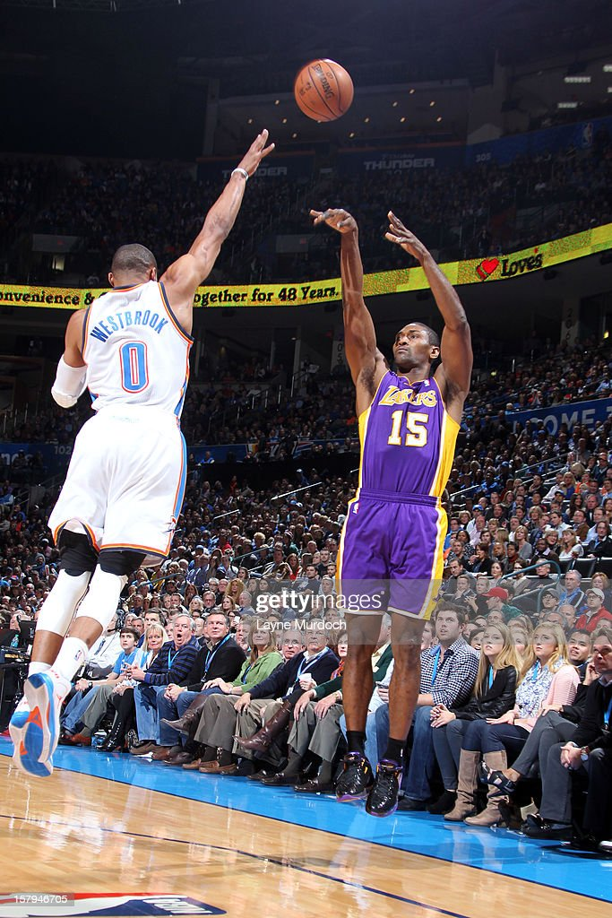 Metta World Peace #15 of the Los Angeles Lakers shoots a three point shot against Russell Westbrook #0 of the Oklahoma City Thunder during an NBA game on December 7, 2012 at the Chesapeake Energy Arena in Oklahoma City, Oklahoma.