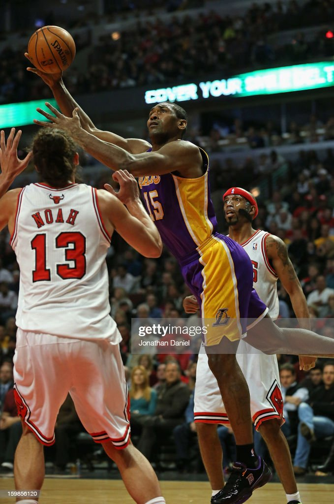 Metta World Peace #15 of the Los Angeles Lakers shoots between Joakim Noah #13 and Richard Hamilton #32 of the Chicago Bulls at the United Center on January 21, 2013 in Chicago, Illinois.