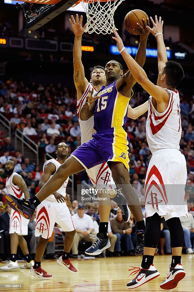 Metta World Peace #15 of the Los Angeles Lakers takes a shot over Carlos Delfino #10 and Jeremy Lin #7 of the Houston Rockets at Toyota Center on January 8, 2013 in Houston, Texas.