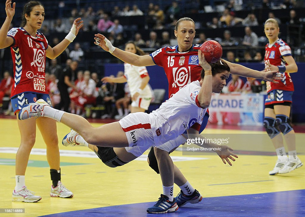 Mette Gravholt (C) of Denmark throws to score near Jelena Eric (R) and Sanja Damjanovic (L) of Serbia during the Women's European Handball Championship 2012 Group I main round match between Serbia and Denmark at Arena Hall on December 11, 2012 in Belgrade, Serbia.