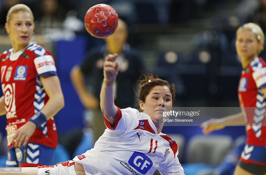 Mette Gravholt (C) of Denmark throws to score near Sanja Rajovic (L) of Serbia during the Women's European Handball Championship 2012 Group I main round match between Serbia and Denmark at Arena Hall on December 11, 2012 in Belgrade, Serbia.