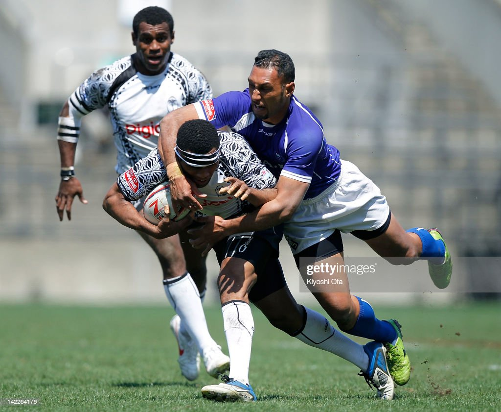 Metuisela Talebula (C) of Fiji is tackled by <a gi-track='captionPersonalityLinkClicked' href=/galleries/search?phrase=Lolo+Lui&family=editorial&specificpeople=577160 ng-click='$event.stopPropagation()'>Lolo Lui</a> (R) of Samoa in the Cup Quarter Final match between Samoa and Fiji during day two of the Tokyo Sevens at Prince Chichibu Stadium on April 1, 2012 in Tokyo, Japan.
