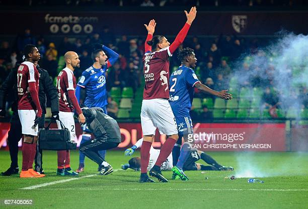 Metz' and Lyon's players reacts after a firecracker has exploded on the pitch during the French L1 football match between Metz and Lyon on December 3...