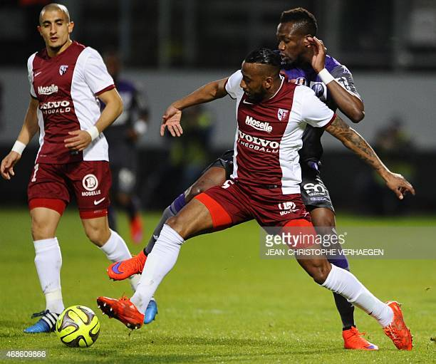 Metz' French defender Romain Metanire vies for the ball with Toulouse's Malian defender Tongo Doumbia during the French L1 football match between...