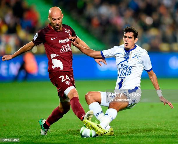 Metz' French midfielder Renaud Cohade vies for the ball with Troyes' French midfielder François Bellugou during the French L1 football match between...