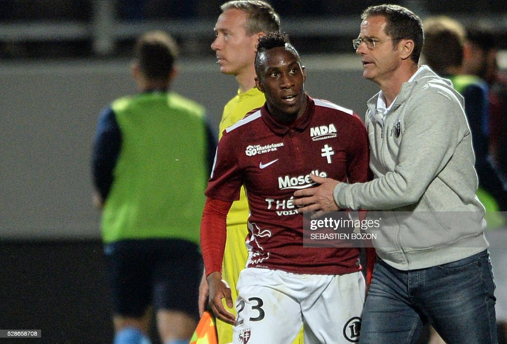 Metz' French midfielder Yeni Ngbakoto (C) is congratulated by Metz' French coach Philippe Hinschberger (R) after scoring a goal during the French L2 football match between Metz vs Tours at the Saint-Symphorien stadium in Longeville les Metz, eastern France, on May 6, 2016. / AFP / SEBASTIEN