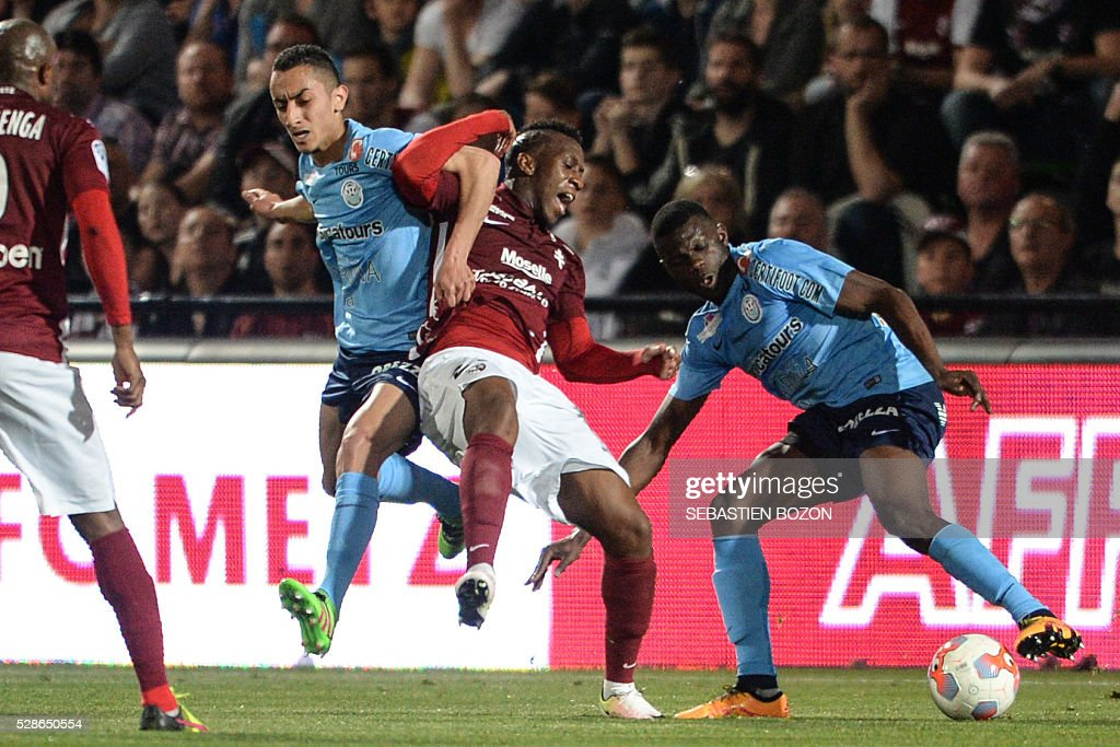 Metz' French midfielder Yeni Ngbakoto (C) vies for the ball with Tours' French midfielder Saif-Edddine Khaoui (L) and Tours' French defender Drissa Diakite (R) during the French L2 football match between Metz vs Tours at the Saint-Symphorien stadium in Longeville les Metz, eastern France, on May 6, 2016. / AFP / SEBASTIEN
