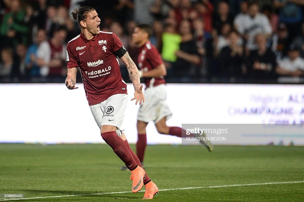 Metz' Italian defender Guido Milan (L) celebrates after scoring a goal during the French L2 football match between Metz vs Tours at the Saint-Symphorien stadium in Longeville les Metz, eastern France, on May 6, 2016. / AFP / SEBASTIEN