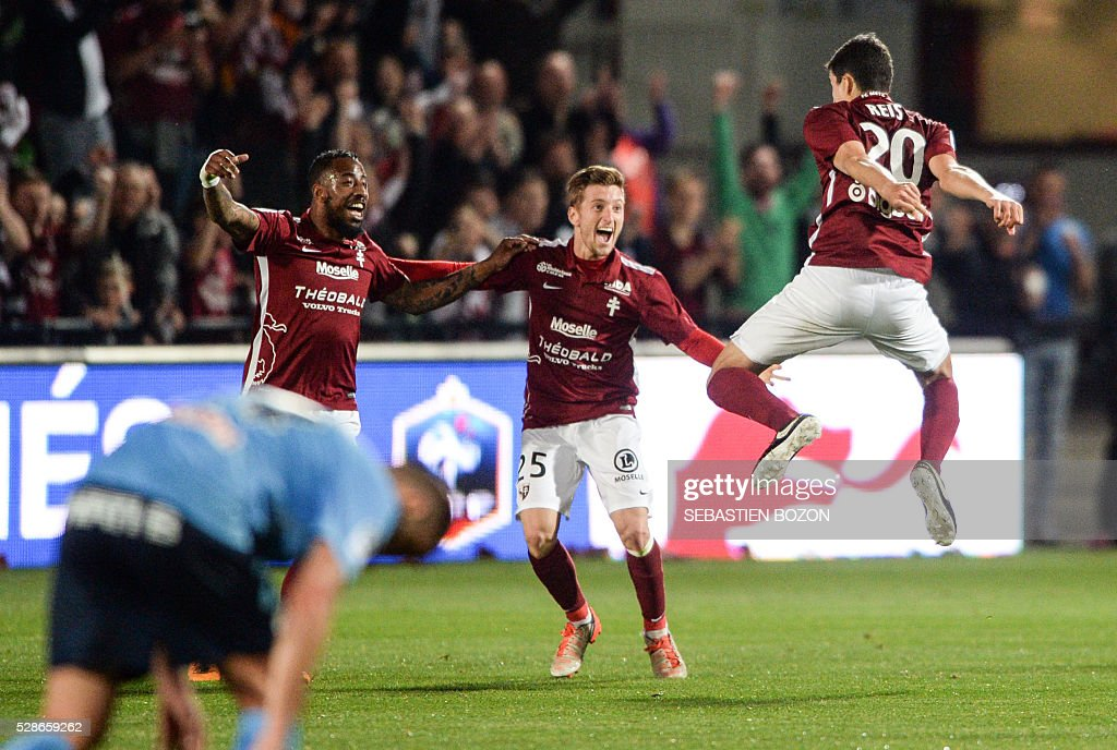 Metz' Spanish defender Ivan Balliu (C) and Metz' Portugese defender Nuno Reis (R) jubilates at the end of the French L2 football match between Metz and Tours at the Saint-Symphorien stadium in Longeville les Metz, eastern France, on May 6, 2016. / AFP / SEBASTIEN