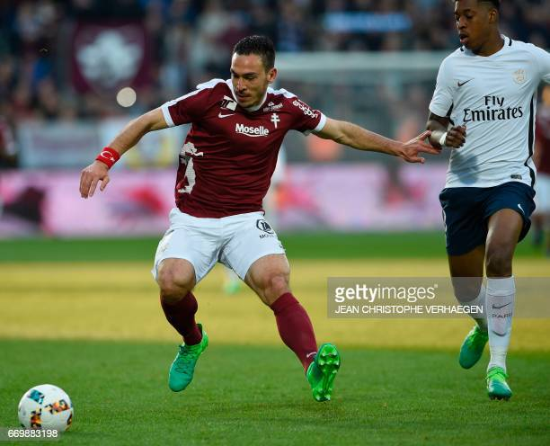 Metz' Turkish forward Mevlut Erding vies for the ball with Paris SaintGermain's French defender Presnel Kimpembe during the French L1 football match...