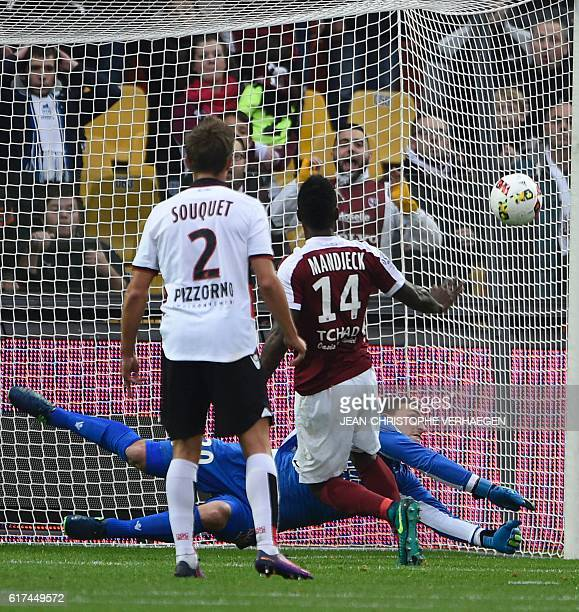 Metz's Cameroonian midfielder Georges Mandjeck scores a goal as Nice's French goalkeeper Yoan Cardinale tries to stop the ball during the French L1...