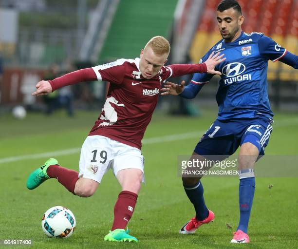 Metz's French midfielder Florent Mollet vies with Lyon's French Algerian midfielder Rachid Ghezzal during the French L1 football match between Metz...