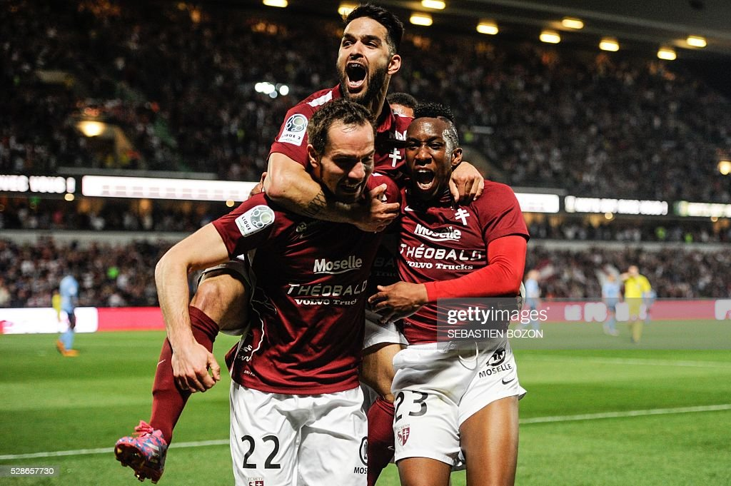 Metz's French midfielder Yeni Ngbakoto (L) celebrates after scoring a goal during the French L2 football match between Metz vs Tours at the Saint-Symphorien stadium in Longeville les Metz, eastern France, on May 6, 2016. / AFP / SEBASTIEN