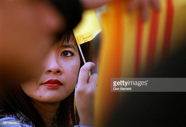 MEVietnameseEyeDB022299––Westminster–– Through layers of yellow and red flags of the former S Vietnam a young woman keeps an eye on the peaceful but...