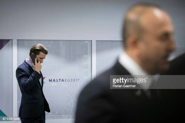 Mevluet Cavusoglu Foreign Minister of Turkey is pictured in front of Sebastian Kurz Foreign Minister of Austria who is seen on the phone before the...