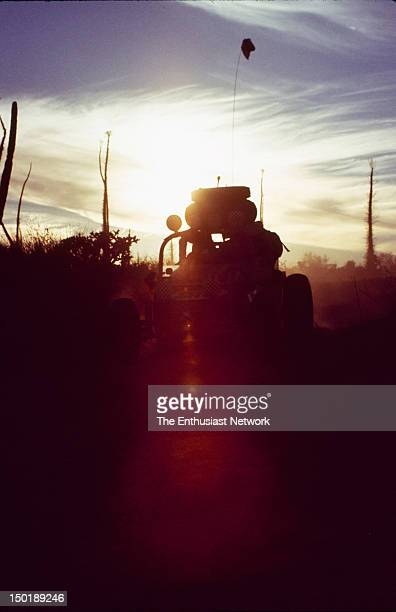 Mexican 1000 OffRoad Race Silhoetted by the setting sun an openwheel buggy Spare front and rear tires sit on top of roll cage Cactus dust and clouds...