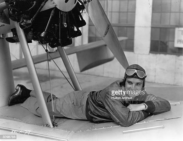 Mexican actor Ramon Novarro sits beneath his aircraft between takes of the MGM film 'Flying Ensign' aka 'Flying Fleet'