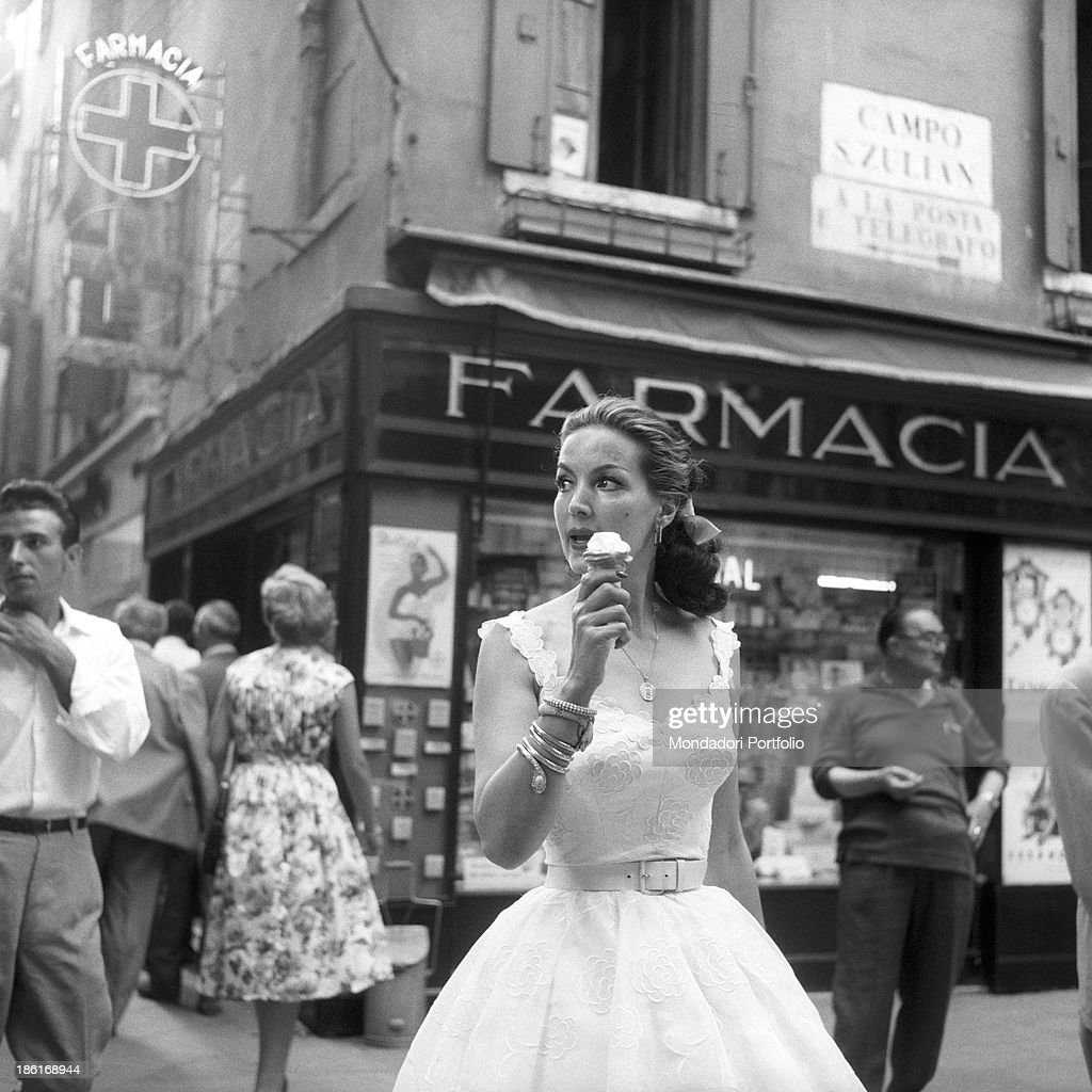 Mexican actress Maria Félix eating an ice cream in front of a pharmacy in Campo San Zulian. She's taking part in the Venice Film Festival. Venice, August 1959.