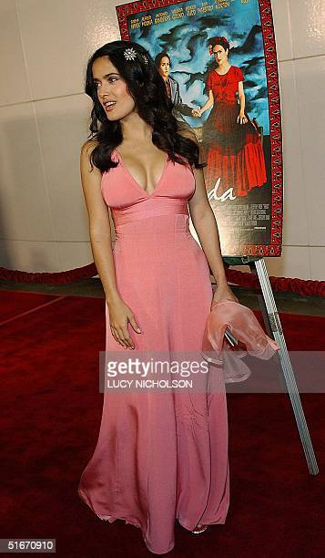 Mexican actress Salma Hayek pose in front of a movie poster depicting her as the Mexican painter Frida Kahlo as she arrives for the premiere of her...