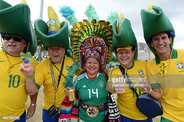 Mexican and Brazlian fans pose on arrival for a Group A football match between Brazil and Mexico in the Castelao Stadium in Fortaleza during the 2014...