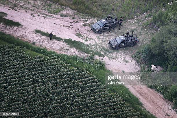 Mexican Army troops stand guard on the Mexican side of the Rio Grande at the USMexico border on May 21 2013 near McAllen Texas The Rio Grande Valley...