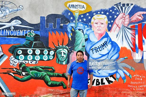 Mexican artist Luis Sotelo poses in front of his worh a mural paint called 'We are migrants not criminals' in Tonatico Mexico on 25 June 2016 The...