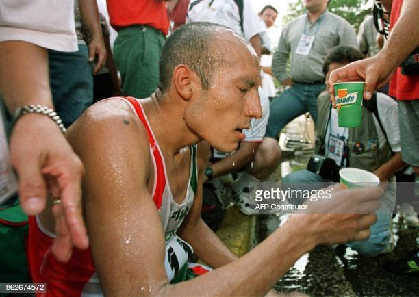 Mexican athlete Juan Camacho pours water over his head 22 August after winning the gold medal in the marathon in Maracaibo Venezuela during the...