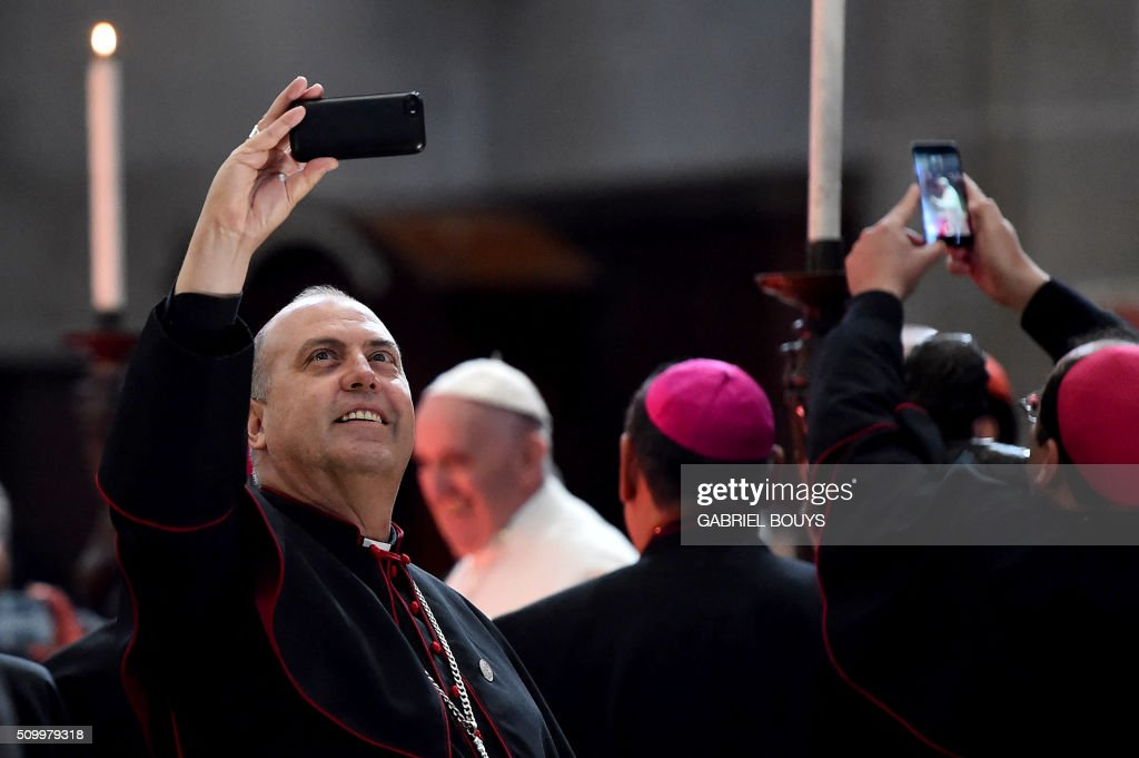 Mexican bishops take snapshots as Pope Francis arrives for a meeting with the Bishops of Mexico gathered in the Cathedral in Mexico on February 13, 2016. Pope Francis called on Mexico's leaders Saturday to provide 'true justice' and security to citizens hit by drug violence as he addressed a National Palace packed with politicians. AFP PHOTO / GABRIEL BOUYS / AFP / GABRIEL BOUYS