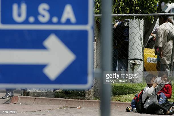 Mexican boy eats from a bowl with a sign pointing towards the United States in the foreground May 13 2006 in Tijuana Mexico US President George W...