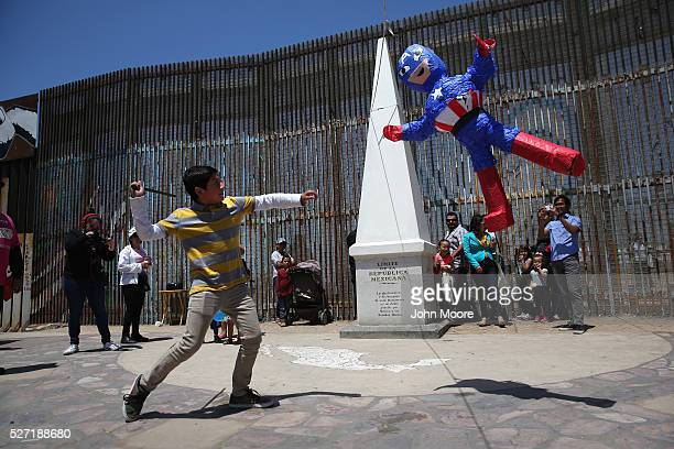 Mexican boy hits a 'Captain America' pinata as part of a weekend of Mexican Children's Day celebrations at the USMexico border on May 1 2016 in...