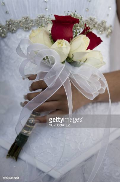 A Mexican bride holds a bouquet during a mass wedding in Mexico City on Valentine's Day on February 14 2014 About 1500 couples were married in a...