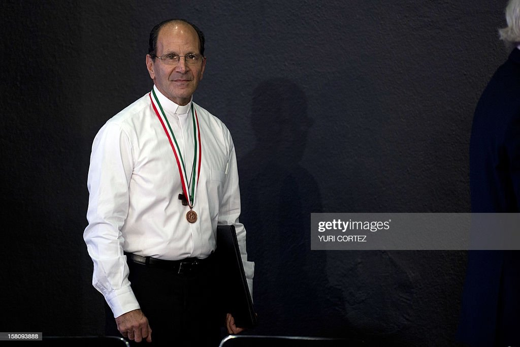 Mexican Catholic priest Alejandro Solalinde attends a ceremony in which he was decorated by Mexican President, Enrique Pena Nieto (out of frame), with the National Human Rights Award at Los Pinos Presidential Palace in Mexico City on December 10, 2012. Solalinde is the founder and director of 'Brothers on the Road' shelter in Oaxaca, Mexico, which dedicates to defend the rights of migrants, receiving some 200 per day. AFP PHOTO/ YURI CORTEZ