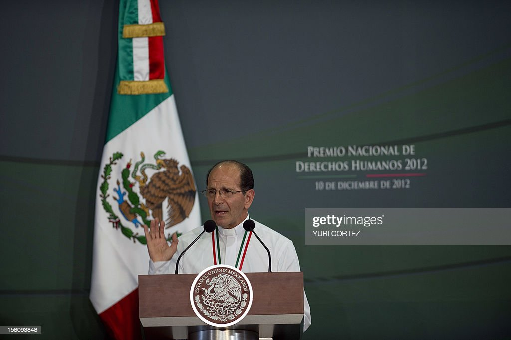 Mexican Catholic priest Alejandro Solalinde delivers a speech during a ceremony in which he was decorated by Mexican President, Enrique Pena Nieto (out of frame), with the National Human Rights Award at Los Pinos Presidential Palace in Mexico City on December 10, 2012. Solalinde is the founder and director of 'Brothers on the Road' shelter in Oaxaca, Mexico, which dedicates to defend the rights of migrants, receiving some 200 per day. AFP PHOTO/ YURI CORTEZ