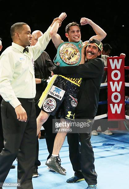 Mexican champion Carlos Cuadras raises his fists in the air after retaining his champion's belt of the WBC super flyweight title boxing match in...