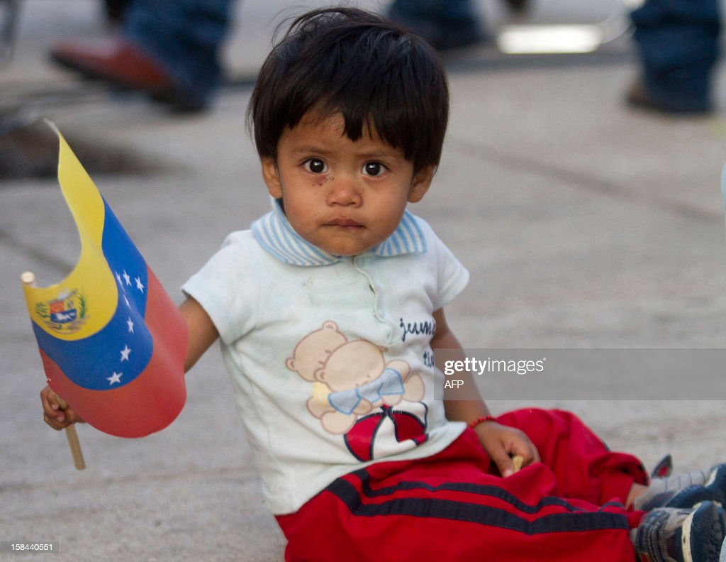 a mexican child holds a venezuelan flag during a demonstration in