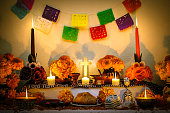 """Traditional mexican Day of the dead altar with cempasuchil flowers, bread """"pan de muerto"""", """"papel picado"""" ornaments and candles."""