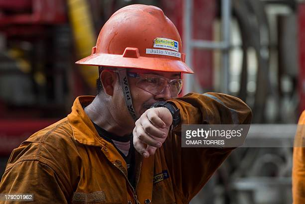 Mexican derrick hand Julio Valencia wipes the sweat from his face after removing the drilling tool with a sample of the marine seabed at La Muralla...