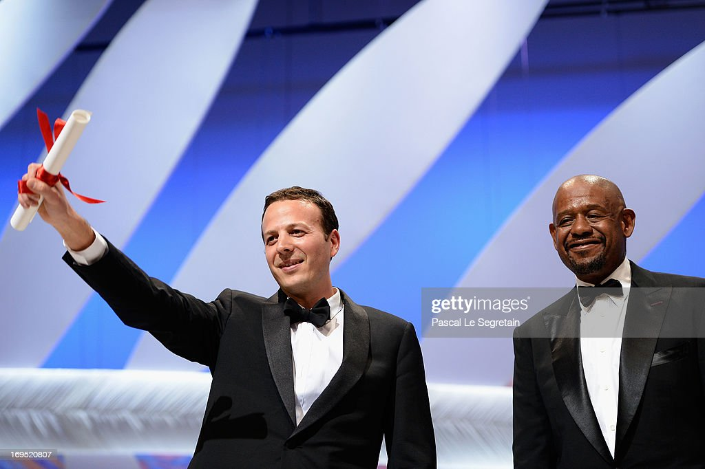 Mexican director Amat Escalante (L) receives the best director award for 'Heli' as actor Forest Whitaker of 'Zulu' watches on stage at Closing Ceremony during the 66th Annual Cannes Film Festival at the Palais des Festivals on May 26, 2013 in Cannes, France.