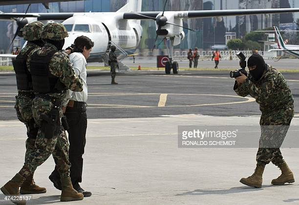 Mexican drug trafficker Joaquin Guzman Loera aka 'el Chapo Guzman' is pictured as he is escorted by marines on February 22 2014 in Mexico City The...
